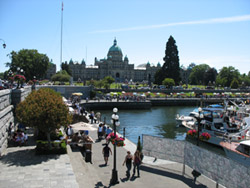 People walking along the walkway of Victoria's Inner Harbour
